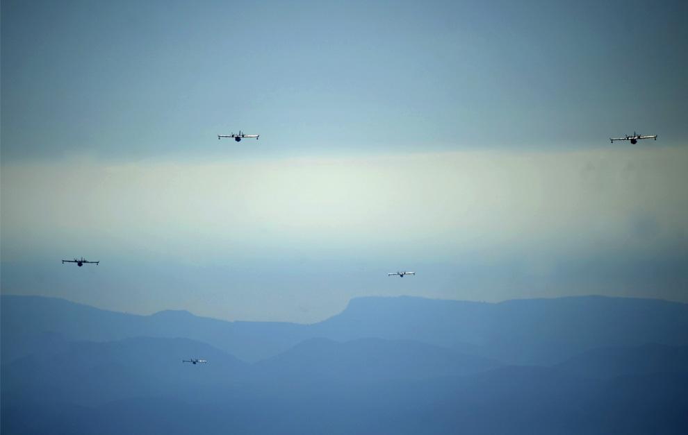 12. Пять самолетов фирмы «Canadair» над лесами Алиаги, неподалеку от Теруэля, Испания, 25 июля 2009. (PEDRO ARMESTRE/AFP/Getty Images)