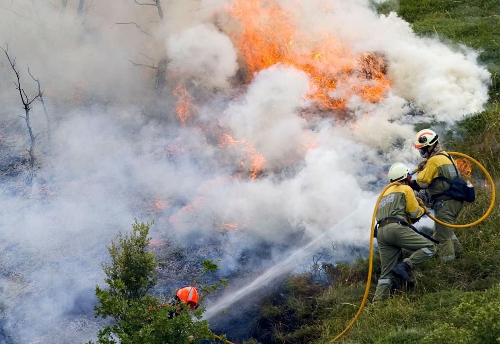 16. Пожарные сражаются с огнем в городе Ларрайоз, Испания, в среду 22 июля 2009 года. (AP Photo/EFE, Villar Lopez)