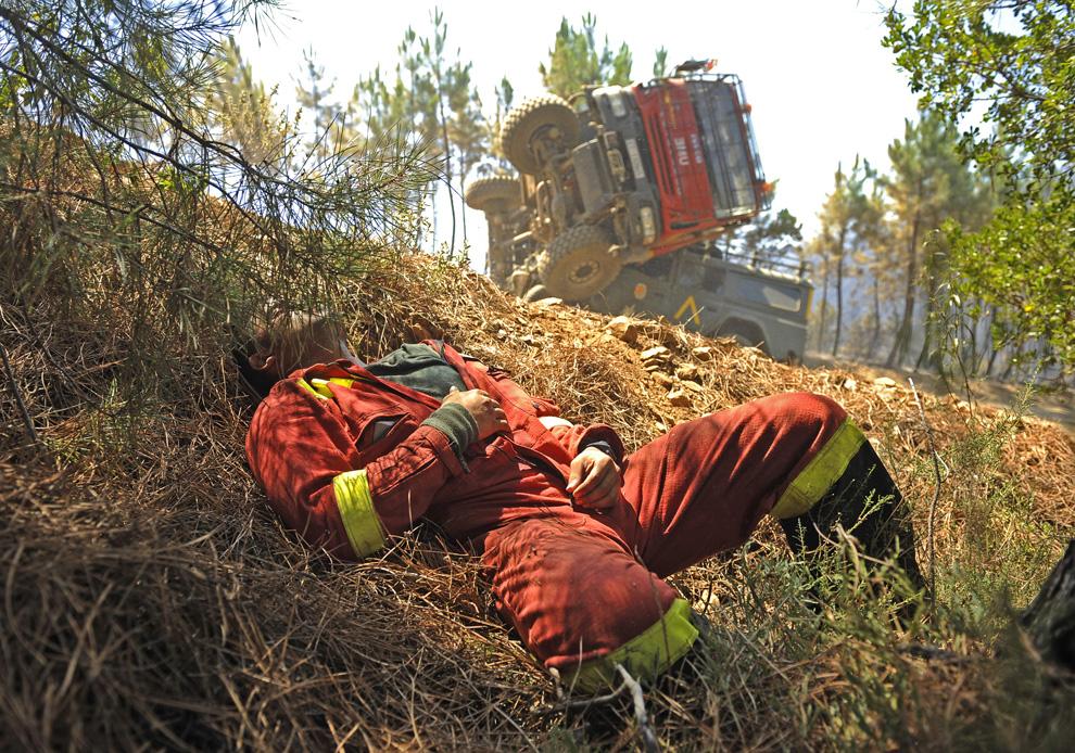 17. Раненый сотрудник испанского отряда по борьбе с чрезвычайными ситуациями лежит на земле, после дорожного происшествия произошедшего во время отчаянной попытки погасить пожар в Вегас де Кория, неподалеку от города Касерес, Испания, 28 июля 2009 года. (PEDRO ARMESTRE/AFP/Getty Images)