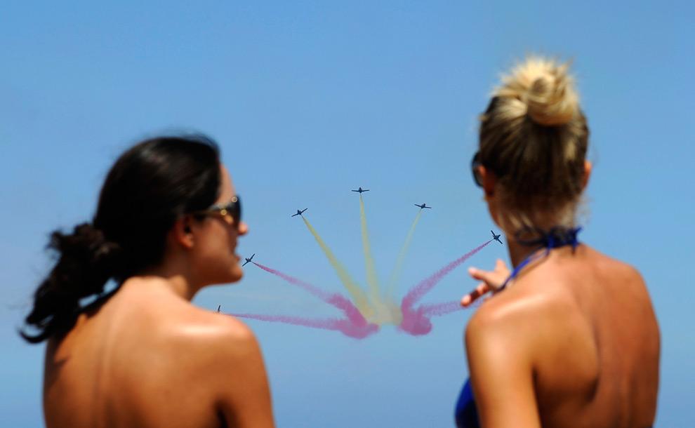 18. Девушки на пляже смотрят, как самолеты «C-101 Aviojet» испанской пилотажной группы «Патрулла Агуила» летят над пляжем Сан Лоренцо в Хихоне, северная Испания, во время авиашоу 26 июля 2009 года. (REUTERS/Eloy Alonso)