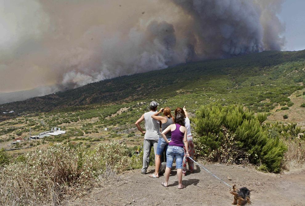 18. Люди наблюдают, как лесной пожар приближается к городу Тигалате на Канарском острове Ла Пальма, Испания, воскресенье, 2 августа 2009. (AP Photo/Carlos Moreno)