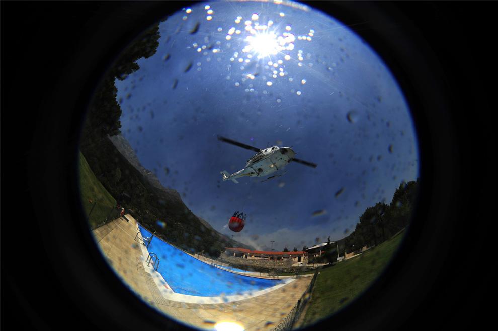 19. Спасательный вертолет набирает воду в бассейне дома в Эль Аренал, неподалеку от Авилы, Испания, так как в регионе бушуют лесные пожары, 29 июля 2009. (PEDRO ARMESTRE/AFP/Getty Images)