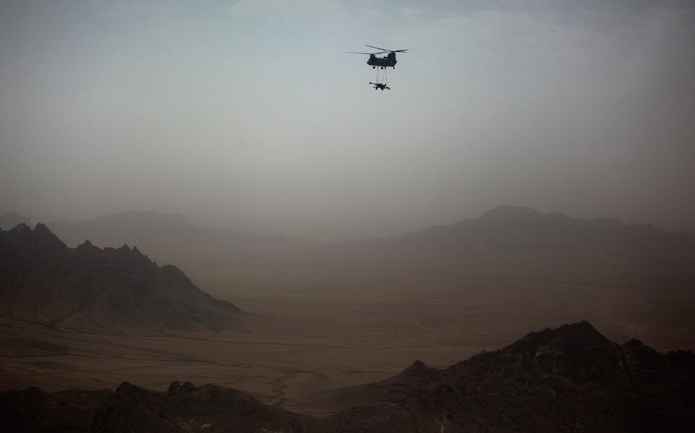 19. Американский вертолет «Чинук» везет гаубицу M777A2 на базу на окраине региона Спин Болдак, примерно в 100 км к юго-востоку от Кабула, в пятницу 31 июля 2009 года. (AP Photo/Emilio Morenatti)