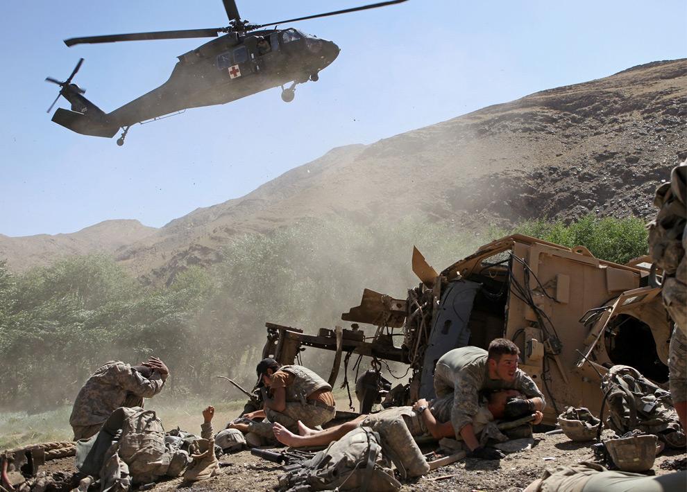 20. На этом снимке, сделанном в среду 19 августа 2009 года, 22-летний сержант второго батальона 87-ой пехоты Пол Пикет из Миндена, Лос-Анджелес, (справа) прикрывает раненого солдата американской армии, пока вертолет приземляется, чтобы забрать раненых. Все это происходит после того, как американский бронетранспортер подорвался в долине Танги афганской провинции Вардак. (AP Photo/David Goldman)