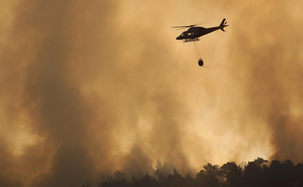 21. Вертолет везет воду, чтобы погасить лесной пожар, бушующий неподалеку от Эль Аренал, Испания, 30 июля 2009. (PIERRE-PHILIPPE MARCOU/AFP/Getty Images)