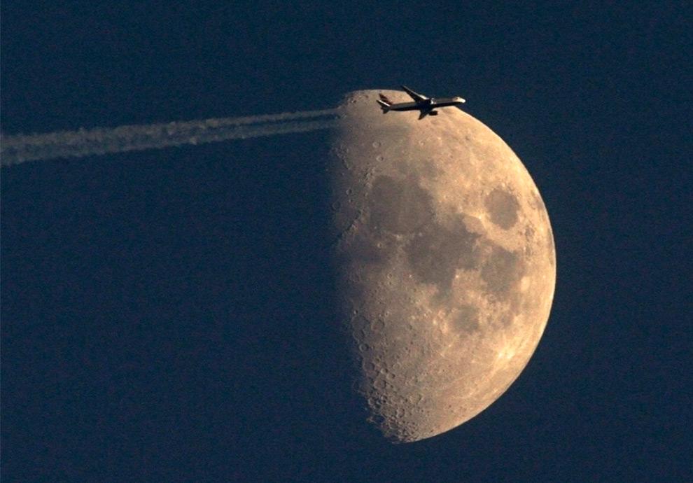 23. Пассажирский самолет компании «British Airways» пролетает на фоне луны над Цюрихом 30 июня 2009. (REUTERS/Arnd Wiegmann)