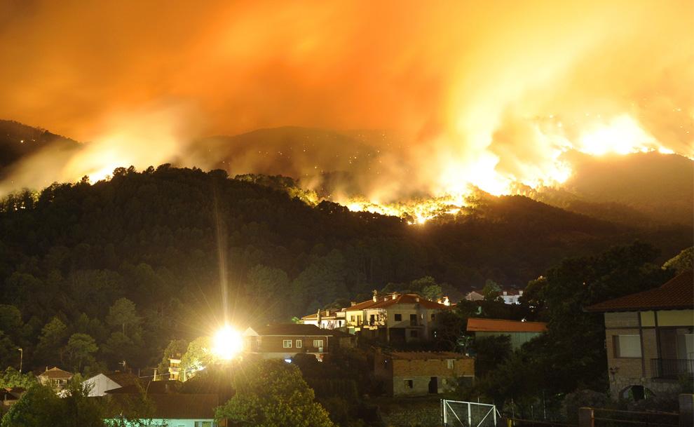 25. Лесной пожар бушует за городом Куэвас-дель-Валье в испанской провинции Авила утром 29 июля 2009 года. (PEDRO ARMESTRE/AFP/Getty Images)