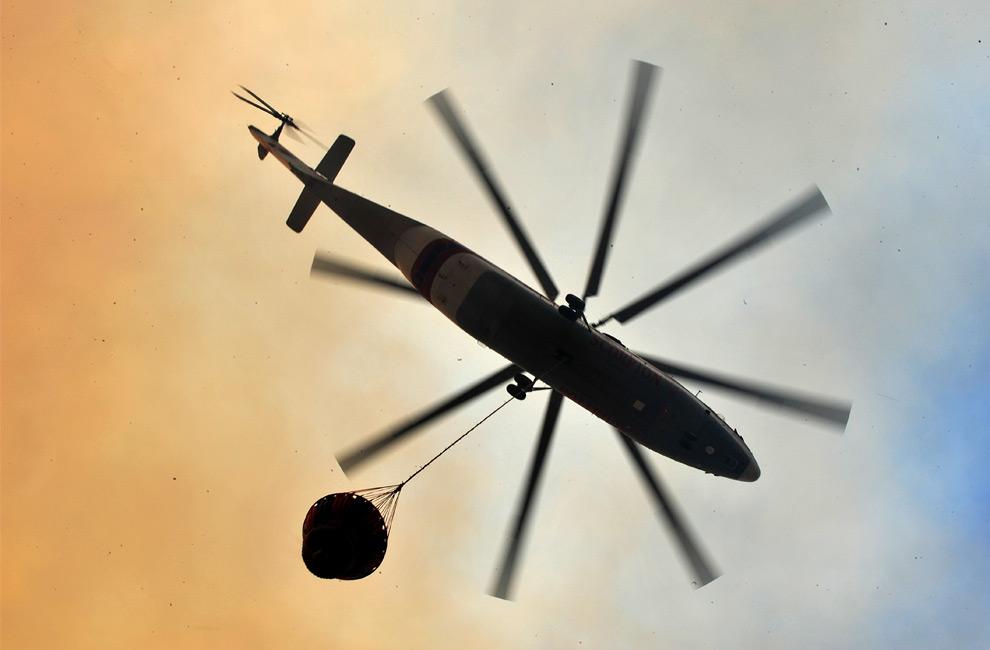 26. Пожарный вертолет летит над деревней Марафон, Греция, 22 августа 2009 года. Власти объявили чрезвычайное положение в связи с бушующими лесными пожарами, которые угрожают домам недалеко от Афин. (LOUISA GOULIAMAKI/AFP/Getty Images)