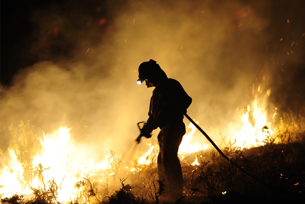 28. Член пожарной бригады города Бельчите работает рядом с линией огня в Андорре утром 23 июля 2009 года. (PEDRO ARMESTRE/AFP/Getty Images)