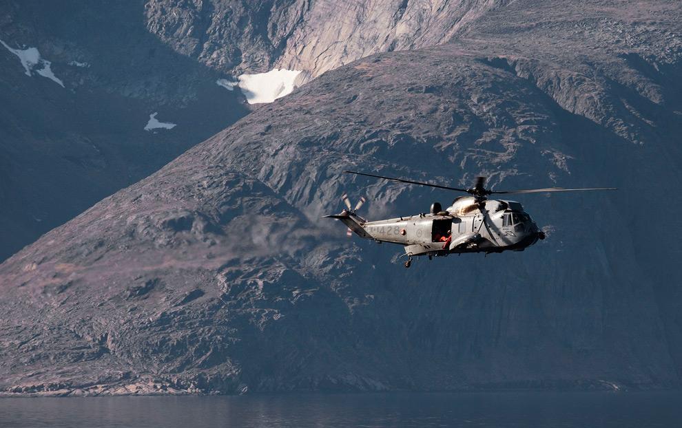 28. Канадский вертолет «CH-124 Sea King» с фрегата канадских ВМС «Торонто» летит над территорией острова Баффин вдоль побережья залива Фробишер в Канадском Арктическом архипелаге 19 августа 2009 года. (REUTERS/Andy Clark)