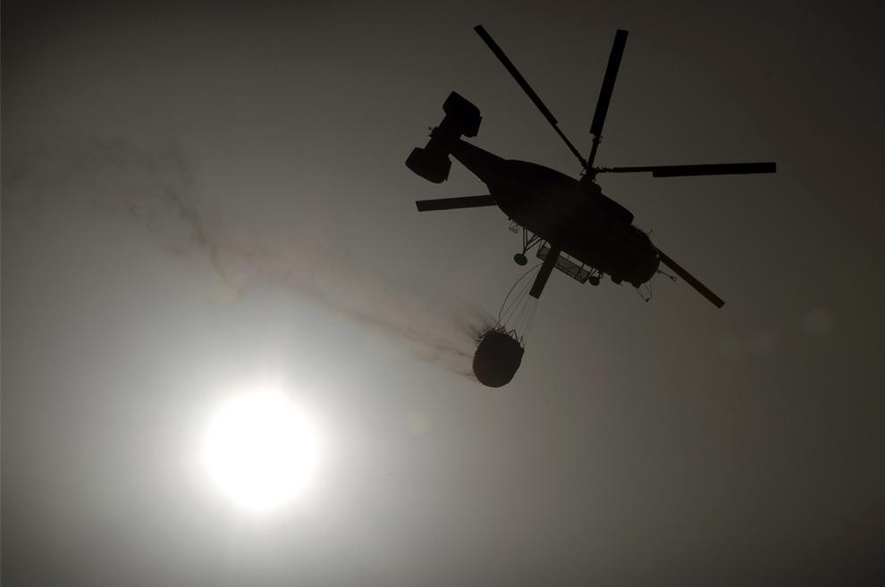 31. Вертолет с емкостью полной воды пролетает на фоне солнца по пути к Мохакару, недалеко от города Альмерия, на юге Испании, где 24 июля 2009 года разгорелся лесной пожар. (Jorge Guerrero/AFP/Getty Images)