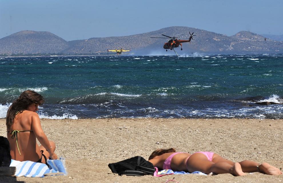 31. Женщины загорают на пляже, в то время как противопожарные самолеты наполняют резервуары водой на курорте Неа Макри в восточных Афинах, 24 августа 2009 года. (LOUISA GOULIAMAKI/AFP/Getty Images)