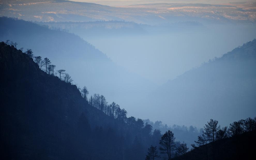 32. Дым собирается в долине города Алиага, недалеко от Теруэля, Испания, 24 июля 2009, после того как накануне здесь прошел сильный пожар. (PEDRO ARMESTRE/AFP/Getty Images)