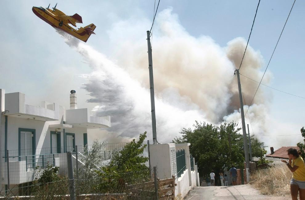 37. Противопожарный самолет сбрасывает воду на лесной пожар в деревне Варнава, к северо-востоку от Афин, Греция, 22 августа 2009 года. (REUTERS/Yiorgos Karahalis)