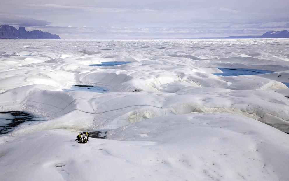 1. Ученый Джейсон Бокс из государственного университета Огайо и эксперт полярной экспедиции Эрик Филипс (оба члены Гринпис) с помощью экспертов в области полярной логистики устанавливают камеру для покадровой съемки 16-километрового ледника Петерманна в северо-восточной части Гренландии 29 июля 2009 года. Корабль организации Гринпис «Арктический рассвет» прибыл в этот район на несколько недель для проведения научных исследований в области изменения климата, а также для наблюдения за разрушением ледника. (NICK COBBING/AFP/Getty Images)