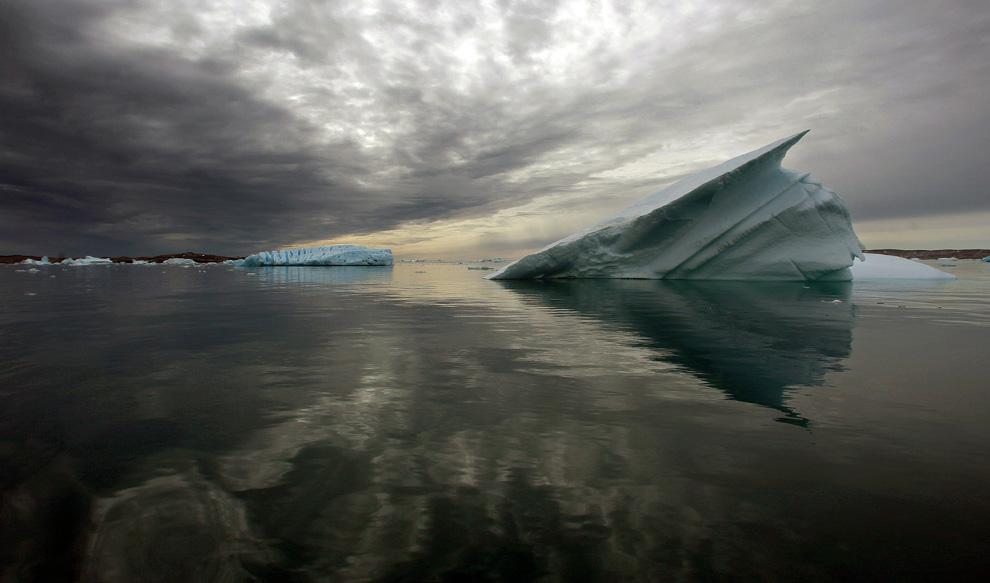 4. Айсберги плывут в спокойных водах фьорда к югу от города Тасиилак в восточной Гренландии 4 августа 2009 года. (REUTERS/Bob Strong)