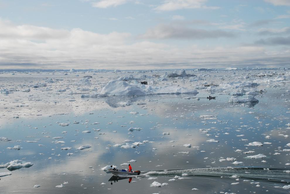 23. Рыбачья лодка разрезает воды ледникового гренландского фьорда Илулиссат в котором полно айсбергов 3 июля 2009 года. (Slim ALLAGUI/AFP/Getty Images)