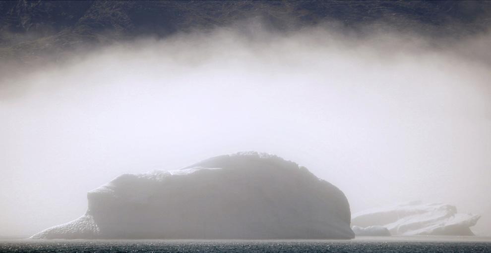 24. Айсберги скрыты завесой раннего утреннего тумана недалеко от южного гренландского городка Нарсак 28 июля 2009 года. (REUTERS/Bob Strong)