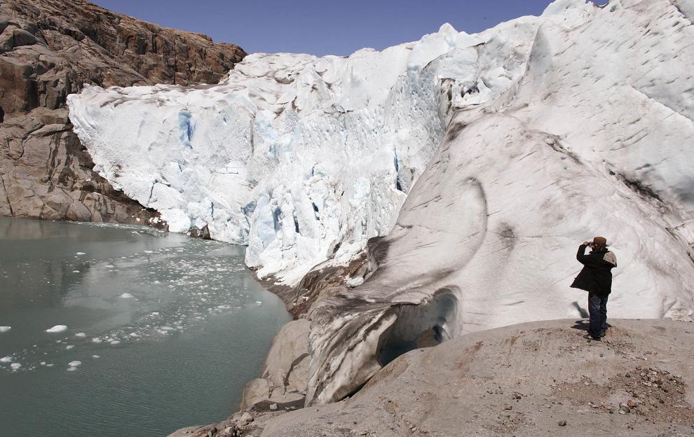 32. Турист фотографирует ледник Близнец недалеко от южного гренландского городка Нарсак 28 июля 2009 года. (REUTERS/Bob Strong)