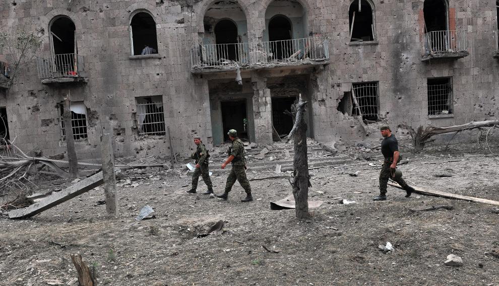 12) Грузинские военные проходят по разрушенному российскими военными силами городу Гори 9го августа 2008 года. Фото: Димитар Дилкофф, AFP