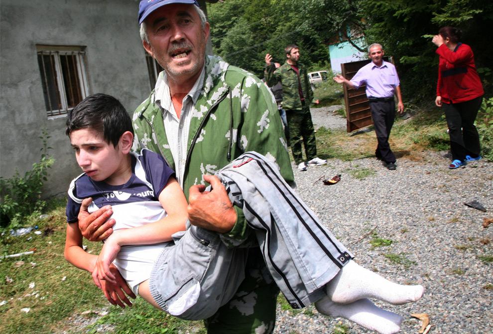 14) Человек с раненым ребенком в югоосетинской столице Цхинвали, 9ое августа 2008 года. Фото: Муса Садулаев, AP photo