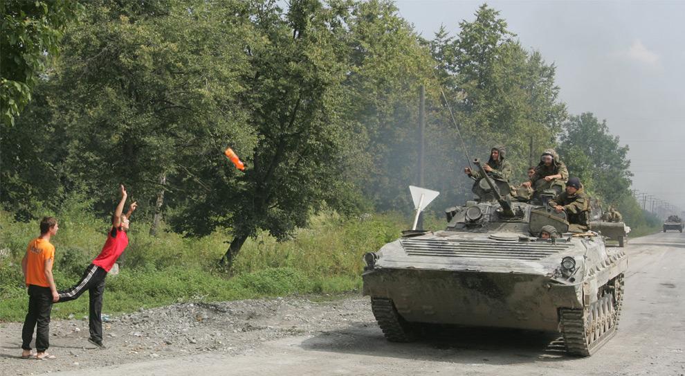 16) Жители Дзуарикау бросают российским военным, двигающимся в место конфликта, сигареты и воду. 9ое августа 2008 года. Фото: Казбек Басаев/AFP/Getty Images