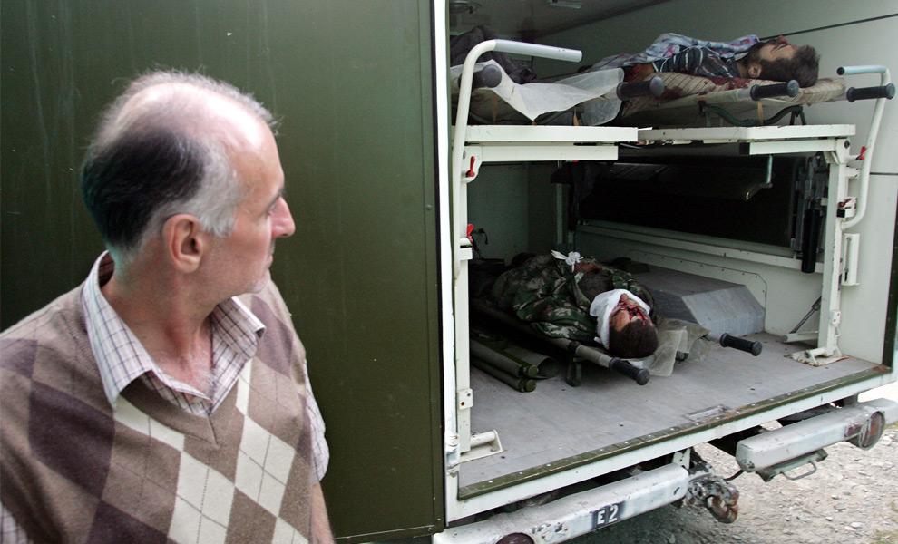 18) Человек смотрит на неизвестных убитых людей, сражавшихся на югоосетинской стороне в городе Джава. 9ое августа 2008 года. Фото: Дмитрий Костюков, AFP