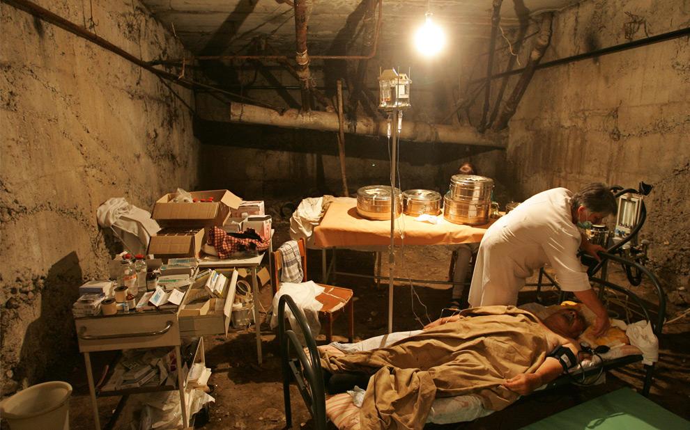 20) Доктор рядом с раненным человеком в подвале разрушенной больницы в Цхинвали. 10ое августа 2008 года. Фото: Дмитрий Костюков, AFP