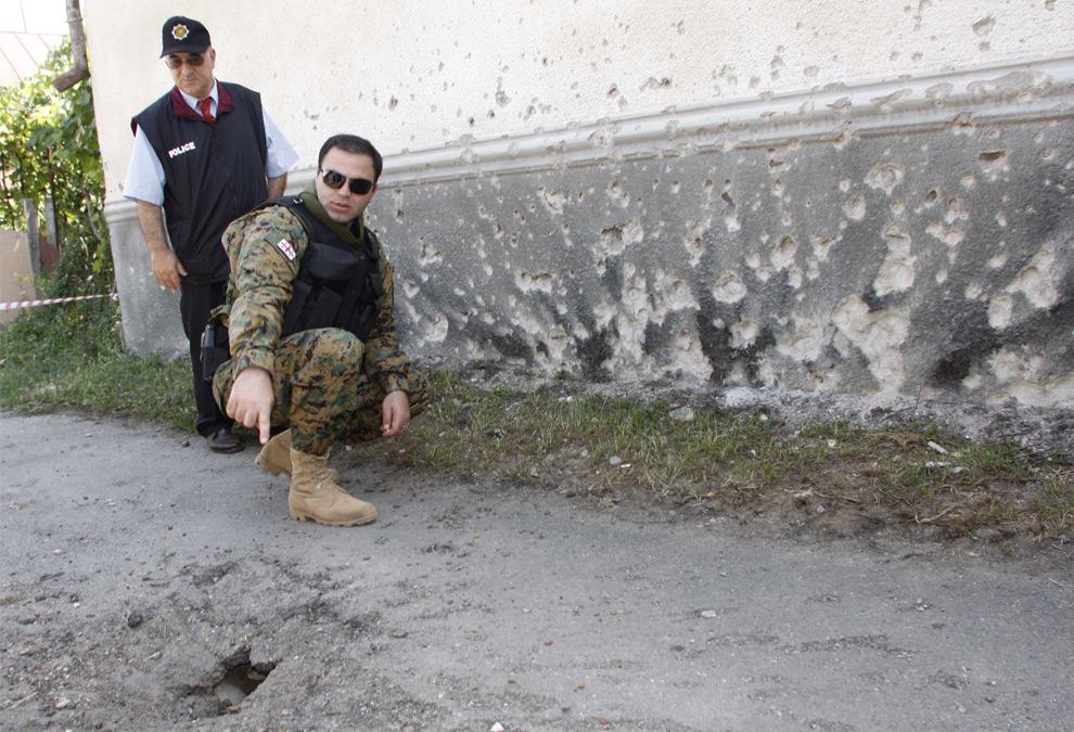 3) Cолдат грузинских миротворческих сил и полицейский показывают след от снаряда, выпущенного с югоосетинской стороны в грузинском селе Никози 5го августа 2008 года. Фото: Георгий Абдаладзе, AP Photo