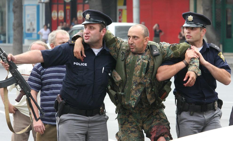 26) Грузинские полицейские помогают раненому солдату в Гори, 8ое августа 2008 года. Фото: Вано Шламов, Getty Images