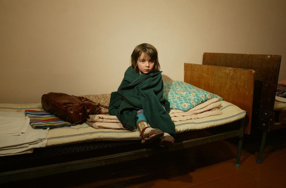 4) Девочка, беженка из Южной Осетии, сидит на кровати во Владикавказе, 4ое августа 2008 года. Фото: Казбек Басаев, AFP