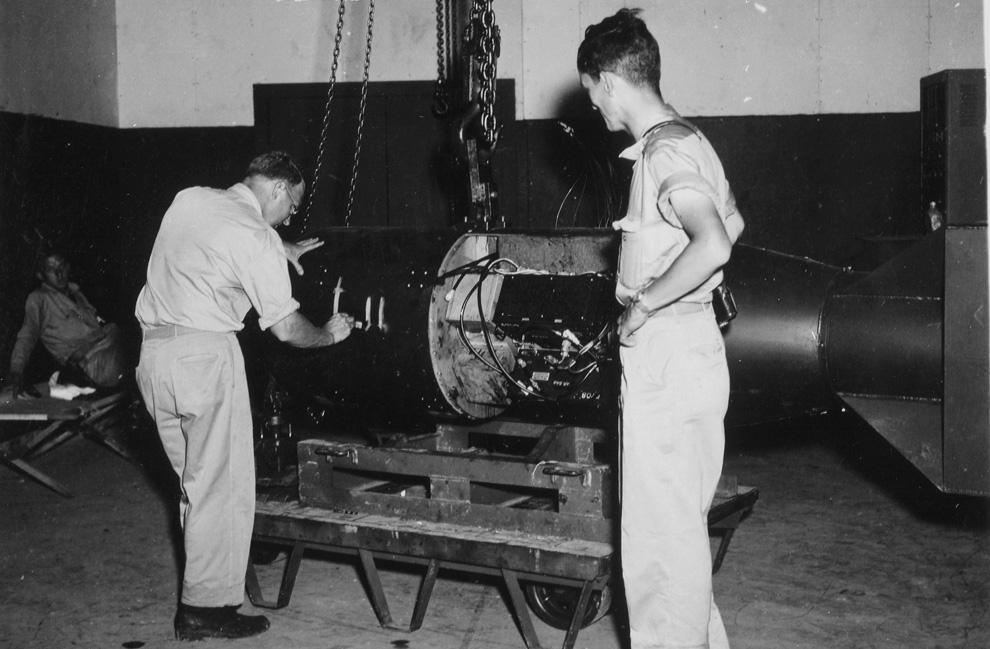 """5. Командир А.Ф. Бирч (слева) нумерует бомбу под кодовым названием «Малыш» перед погрузкой ее на трейлер в здании Ассамблеи №1 перед конечной погрузкой бомбы на борт бомбардировщика B-29 Superfortress """"Enola Gay"""" на базе 509-ой сводной группы на острове Тиниан у Марианских островов в 1945 году. Физик доктор Рамсей (справа) получит Нобелевскую премию в области физики в 1989 году. (U.S. National Archives)"""