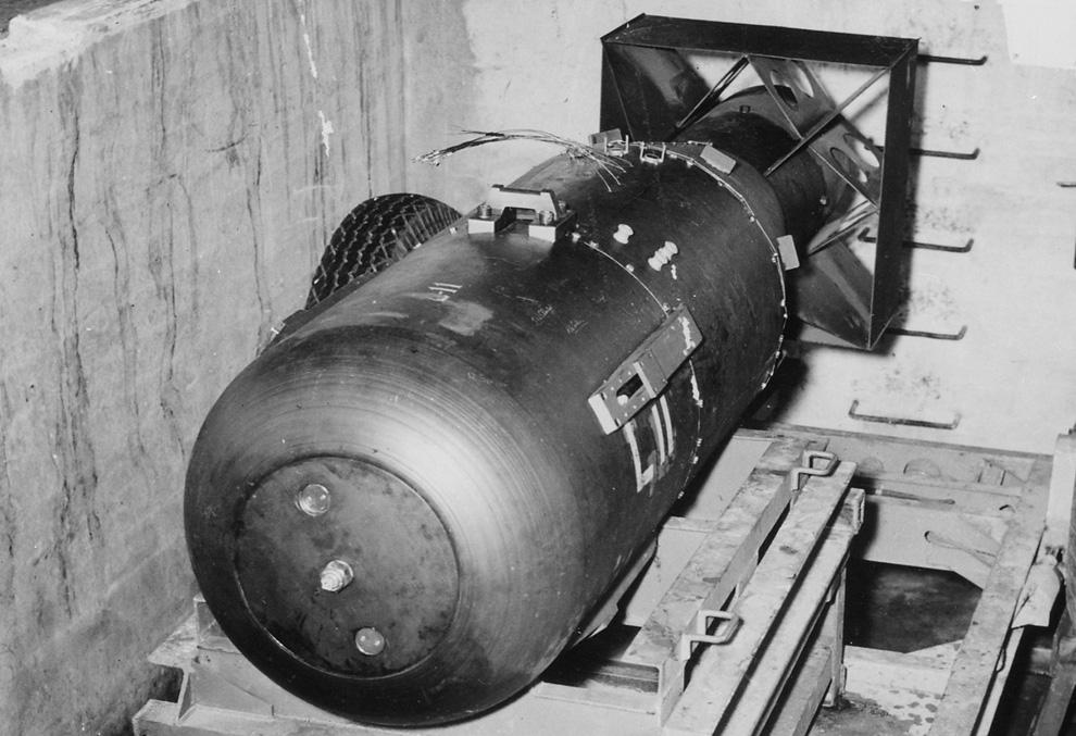 """6. «Малыш» покоится на трейлере в яме над шлюзом бомбардировщика B-29 Superfortress """"Enola Gay"""" на базе 509-ой сводной группы на ÐœÐ°Ñ€Ð¸Ð°Ð½ÑÐºÐ¸Ñ Ð¾ÑÑ'Ñ€Ð¾Ð²Ð°Ñ Ð² 1945 году. «Малыш» составлял 3 м в длину и весил 4 000 кг, но содержал всего 64 кг урана, который использовался для провоцирования цепочки аÑ'Ð¾Ð¼Ð½Ñ‹Ñ Ñ€ÐµÐ°ÐºÑ†Ð¸Ð¹ и последующего взрыва. (U.S. National Archives)"""