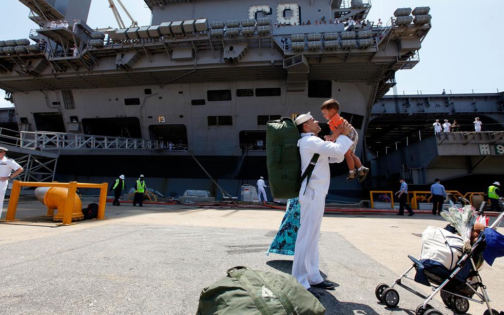 1. Моряк Элиэзер Арройо держит на руках 23-месячного сына Элиэзера младшего, сойдя с палубы авианосца Эйзенхауэр по прибытии его в Норфолк, штат Вирджиния, 30 июля. Авианосец Эйзенхауэр (CVN 69) с 6 000 моряков на борту вернулся в родной порт после пятимесячной операции «Несокрушимая свобода» в пятом отделении флота, ответственном за морскую безопасность. (Getty Images/Mark Wilson)