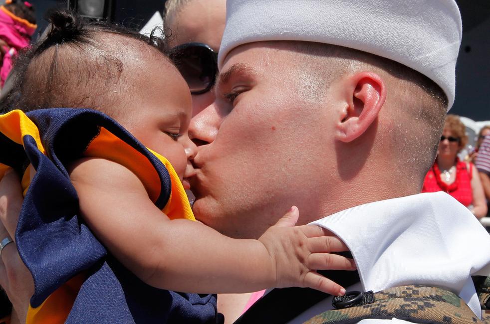 3. Моряк Сэмюэль Миллиен целует свою четырехмесячную дочь Тару Миллиен, впервые увидев ее после прибытия авианосца Эйзенхауэр в Норфолк, Вирджиния, 30 июля. (Getty Images/Mark Wilson)
