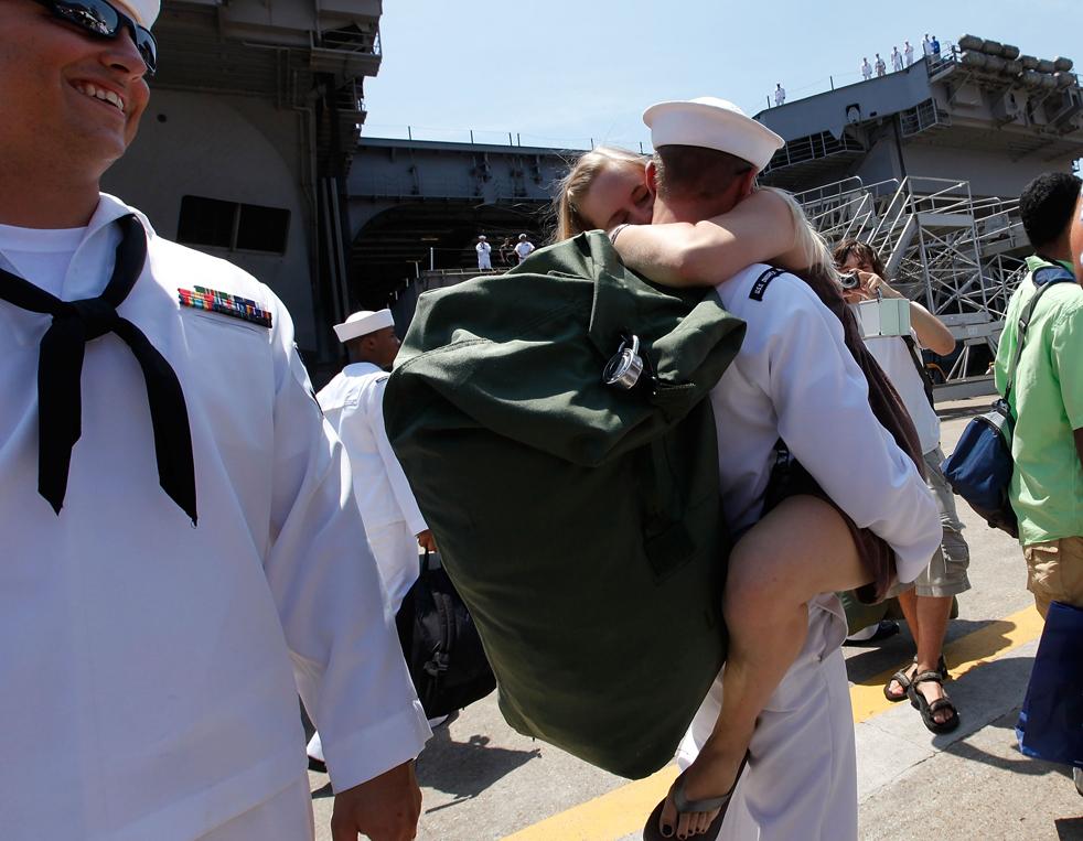 7. Моряк Эндрю ВанВинкл обнимает жену Джану по прибытии в Норфолк, Вирджиния, на авианосце Эйзенхауэр 30 июля. (Getty Images/Mark Wilson)