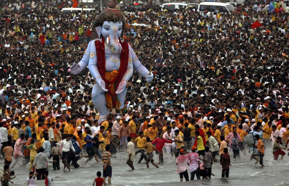 1) Верующие несут статую бога процветания Ганеша в образе слона, чтобы погрузить ее в море в последний день праздника Ганеша Чатуртхи в Мумбай 14 сентября 2008 года. Глиняная статуя Ганеша изготавливается за два-три месяца до этого религиозного индийского фестиваля. Идолов несут по улицам длинной процессией, сопровождаемой песнями и танцами, к реке, где они будут погружены в воду; это символизирует ритуальные проводы божества в путешествие к своему обиталищу.