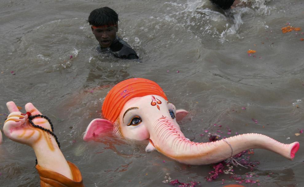 2) Верующий наблюдает за погружением бога-слона Ганеша в воды реки Сабармати в последний день праздника Ганеша Чатуртхи в западном городе Индии Ахмедабаде 14 сентября 2008 года.