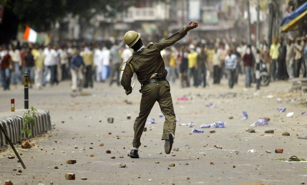 8) Полицейский бросает камни в протестующих в городе Джамму, Индия, воскресенье 31 августа 2008.