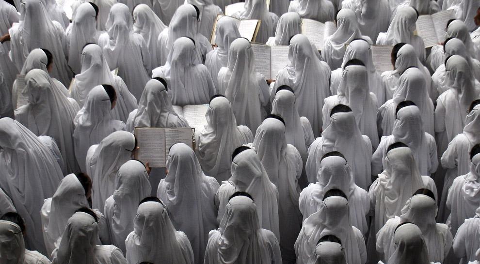 9) Католические монахини благотворительного общества поют специальную молитву во время церемонии, посвященной одиннадцатой годовщине смерти Матери Терезы в восточном городе Индии Калькутта 5 сентября 2008 года. Мать Тереза была монахиней, получившей Нобелевскую премию, которая умерла в 1997 году и была причислена к лику блаженных папой Иоанном Павлом вторым в 2003 году в Ватикане.