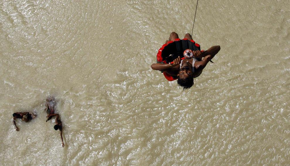 13) Жителя деревни поднимают на военно-спасательном вертолете из района затопленной деревни в восточном штате Бихар 3 сентября 2008 года. Наводнение выгнало из дома более трех миллионов людей, уничтожило 250 000 акров земли и стало причиной гибели более 150 людей.