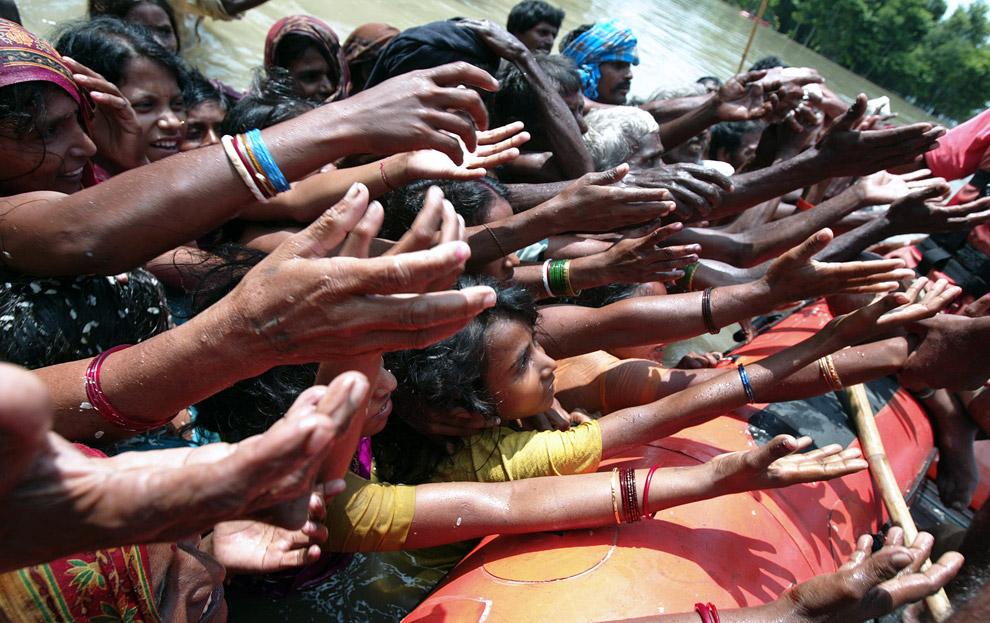 15) Беженцы из пострадавших от наводнения районов тянут руки за едой, предоставляемой представителями Национальной Службы Борьбы с Последствиями Стихийных Бедствий в районе Рагунатпур, округ Мадхепура в северо-восточном штате Бихар 5 сентября 2008 года. Спасатели в северной Индии спасли более 800 000 людей, но остальные десятки тысяч по-прежнему считались в ловушке.