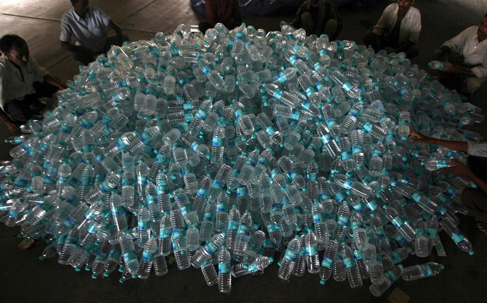 16) Спасатели собирают бутылки с питьевой водой на станции военно-воздушных сил, чтобы сбросить их с самолета в пострадавшие от наводнения районы, в восточном штате Бихар, 3 сентября 2008.