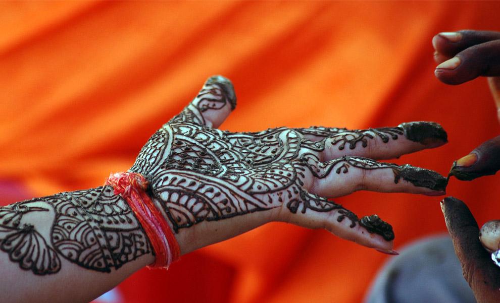 18) Женщине раскрашивают руку хной во время фестиваля Тидж в городе Аллахабад на севере Индии, 2 сентября 2008 год. Во время фестиваля Тидж женщины постятся и молятся за здравие и долголетие своих мужей.