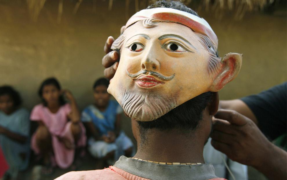 20) На затылок собирателя меда надевают маску, Бали, деревня Сундарбанс, Индия, вторник 5 августа 2008 года. Сундарбанский лес, настоящее сплетение суровых удаленных островов на самом краю востока Индии, является домом для самой большой в мире численности тигров, нападющих на людей, а также четырем миллионам самых бедных людей в Индии. Местные жители верят, что тигр никогда не нападает на человека спереди, поэтому носят на затылке маски, чтобы отпугнуть их.