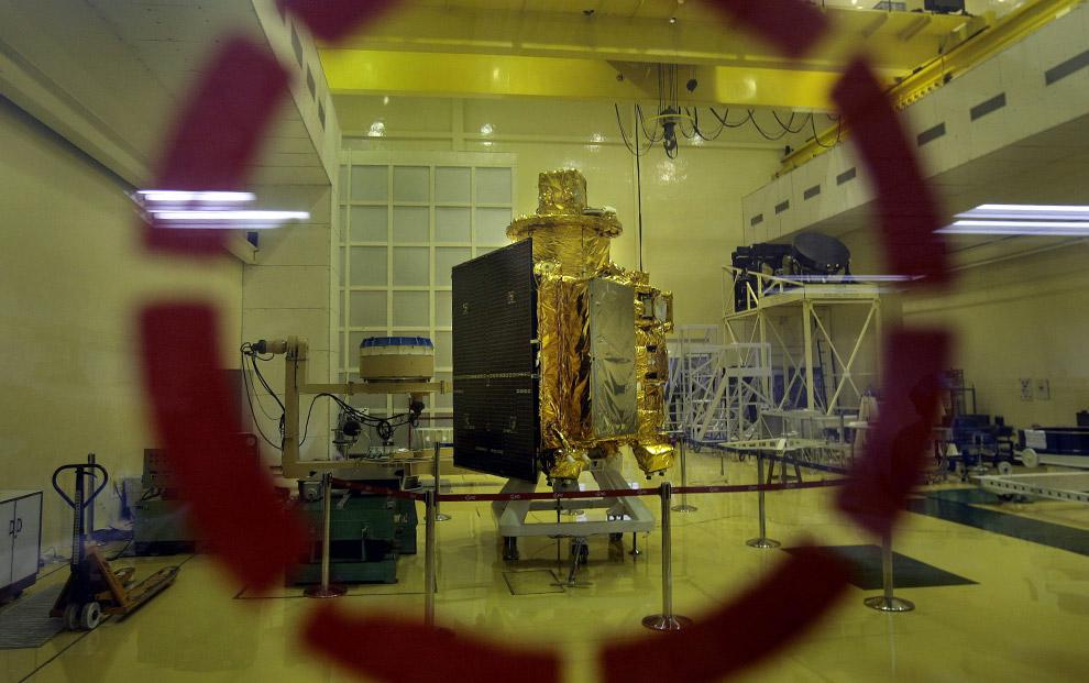 21) Космический зонд Чандраян-1, первый космический летательный аппарат Индии для полетов на Луну; вид из-за стеклянных дверей центра Индийской организации космических исследований в Бангалоре, 18 сентября 2008 года. Чандраян-1 почти дошел до последней стадии разработки, после чего его отправят в центр запуска в космическом центре Сатиш Дхаван в Шрихарикоте.