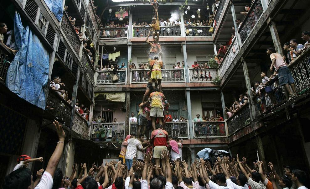 24) Верующие пытаются сделать живую пирамиду, чтобы дотянуться и разбить глиняный кувшин с медом, молоком и творогом, что является частью фестиваля в честь празднования годовщины рождения великого Кришны, Мумбай, Индия, воскресенье 24 августа 2008 года.