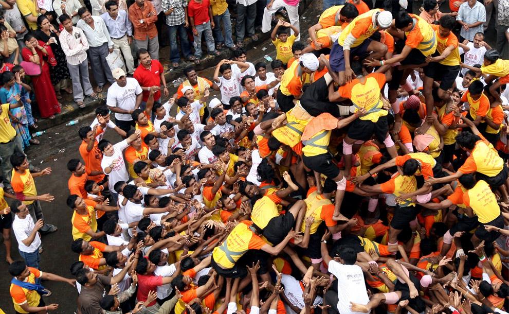 25) Молодые поклонники великого Кришны пытаются сделать семиярусную живую пирамиду во время соревнования «дахи-ханди» в Мумбай 24 августа 2008 года, которое является частью фестиваля Джанмаштами, который знаменует рождение бога Кришны. Сотни почитателей бога Кришны принимают участие в событии «дахи-ханди», во время которого на высоте 20-40 футов развешены кувшины, наполненные молоком, творогом, маслом и фруктами. Отважные молодые люди пытаются достать приз, соорудив пирамиду из людей, чтобы находящийся на самом верху участник смог дотянуться до кувшина и завершить соревнование, разбив его.