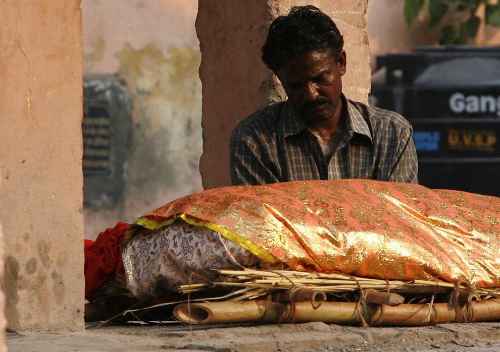 27) Родственник жертвы, погибшей от взрыва бомбы, сидит рядом с телом у крематория в Нью-Дели 14 сентября 2008 года. В воскресенье полицейские прочесали все трущобы и криминальные притоны столицы в поисках подозреваемых в серии бомбардировок в городе, которые произошли днем раньше и убили около 20 человек и ранили более сотни. По меньшей мере, пять бомб взорвались друг за другом на заполненных людьми рынках и улицах прямо в сердце Нью-Дели в субботу ночью.