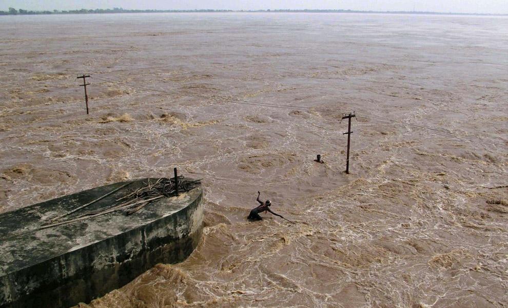 30) Люди вылавливают дерево в хозяйственных целях на плотине Нарай на реке Катходи в восточном индийском штате Орисса в пятницу  19 сентября 2008 года. Согласно агентству новостей, бедственная ситуация в Ориссе ухудшилась, когда правительство провело массовую эвакуацию жителей низколежащих районов.